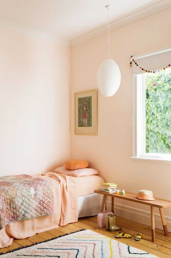 single bed frame with peach comforter peach walls wood plank floors modern area rug with colorful line accents wood bench seat