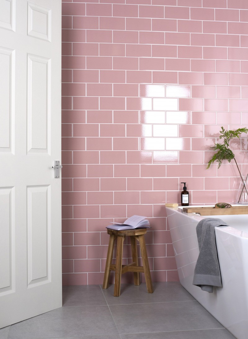 soft blush pink subway tile walls wood stool modern white bathtub some greenery