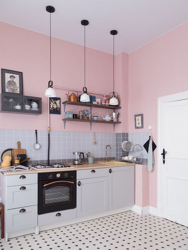 soft pink walls wood shelving units gray tile backsplash white kitchen cabinets