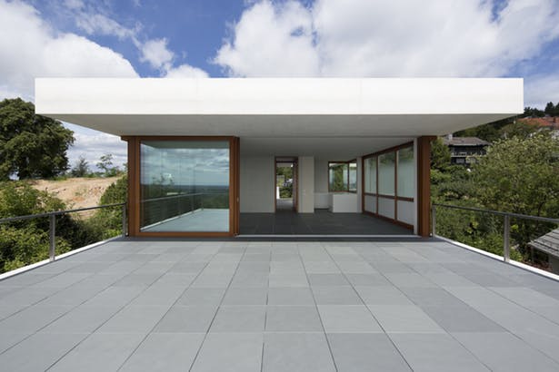 ultra modern villa's exterior consisting of concrete tile floors sliding glass door with wood frame