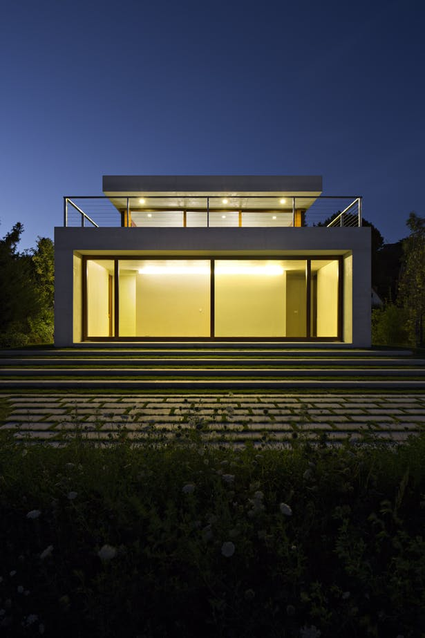 view of villa at night exposing warm and modern lighting