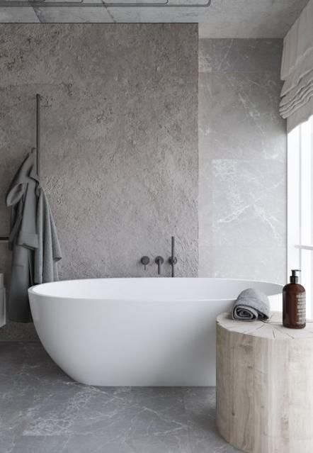 white bathtub light wood trunk stool gray concrete walls with hard texture smooth concrete floors