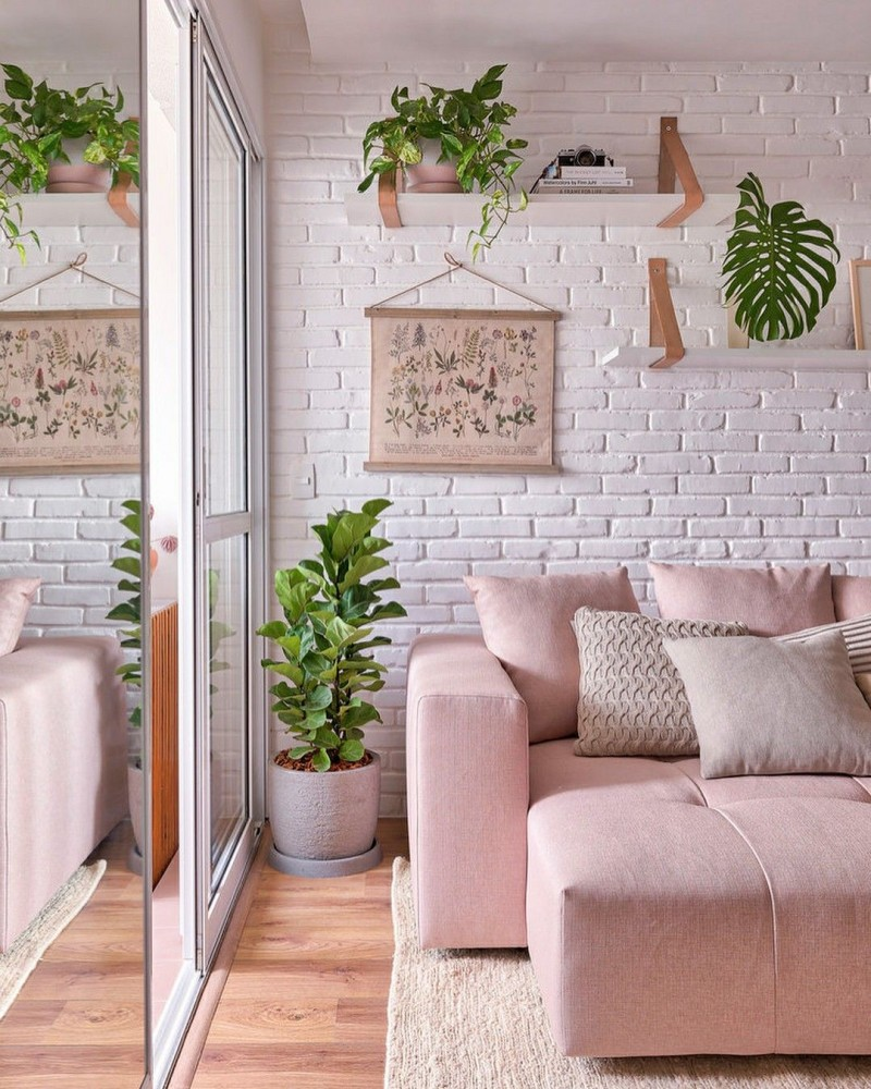 white brick wall soft pink sectional sofa soft toned throw pillows corner greenery on white pot wood floors white area rug