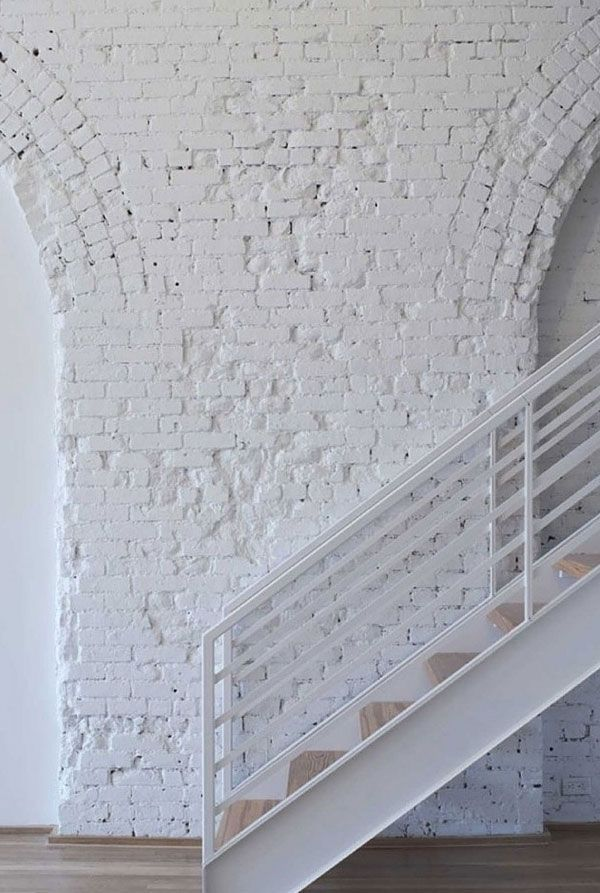 white brick wall staircase with white railings light wood floors