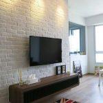 White Brick Wall Wall Mounted TV Dark Wood Media Console Table British Flag Mat Light Wood Floors