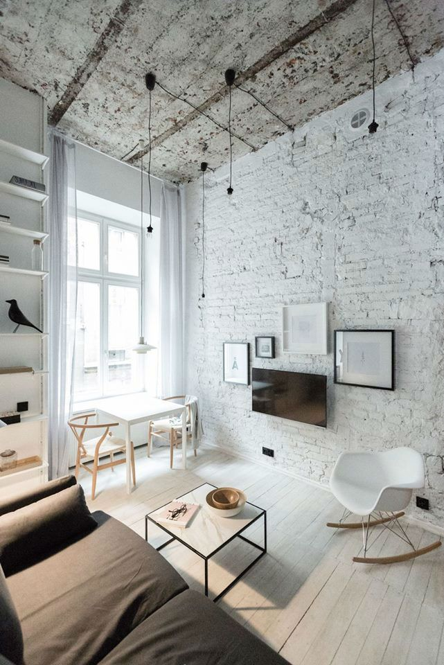 white brick wall worn out white ceilings white wood plank floors small wood table in white a couple of wood chairs white top coffee table with black frame white rock chair