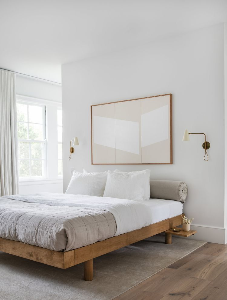 wood bed frame white bedding linen and pillows light gray comforter wood framed wall art wood floors gray area rug