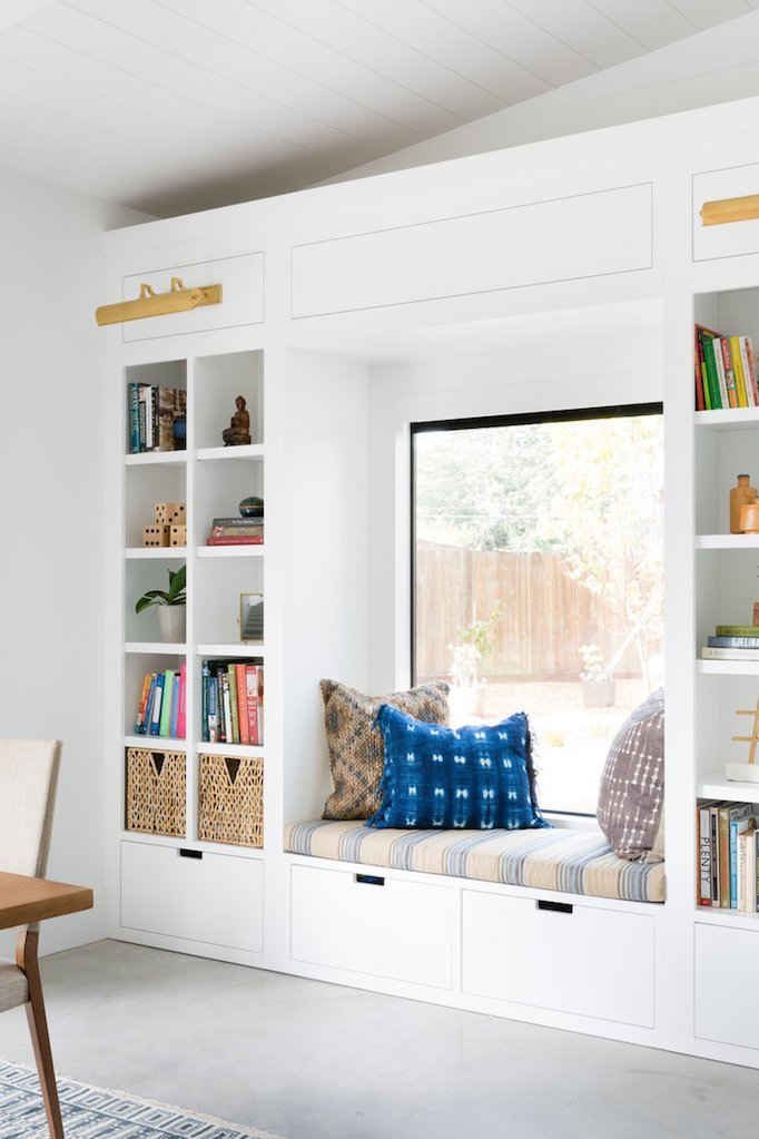 clean and minimalist reading nook with small bay window with cushion and some throw pillows recessed book shelves