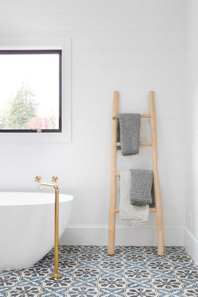 clean white bathroom design with purely white bathtub brass standing shower faucet light wood ladder rack vintage tile floors black framed glass window