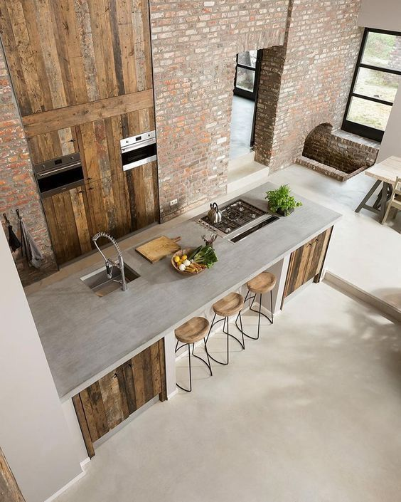 industrial style kitchen and eat in kitchen with concrete countertop industrial bar stools with round wood top brick walls rustic wood cabinets