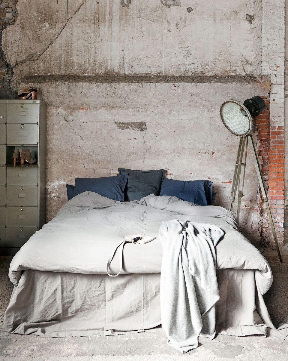 light gray bedding set tripod base floor lamp worn out metal drawer system worn out concrete walls