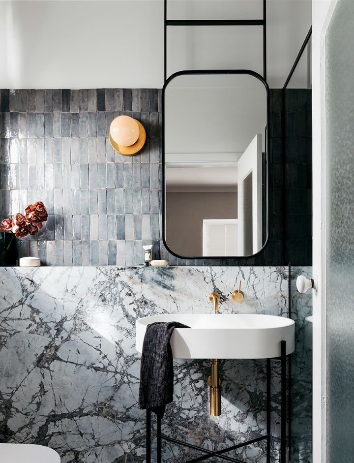marble wall featuring concrete tile wall black framed mirror white bathroom sink with black metal legs brass faucet