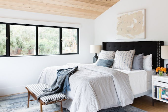 master bedroom design with comfy white bedding set wood bench bed with striped cushion gray throw blanket light toned rug series of glass windows natural wood ceilings