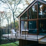 Midcentury Modern Cabin Exterior Design With Glass Windows Wood Deck Plus Minimalist Railings And Nature Surrounds It