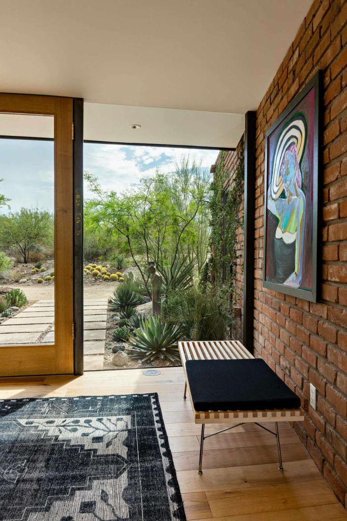 midcentury modern home design with wood bench seat black area rug wood floors sliding glass door