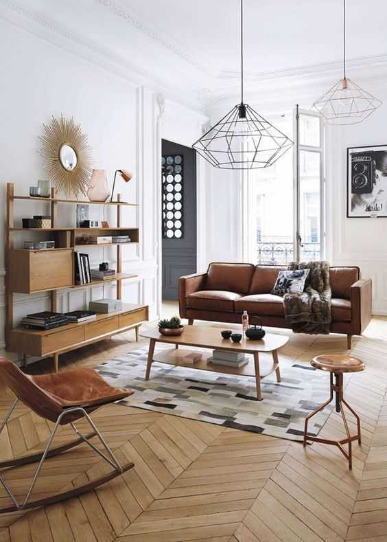 midcentury modern living room with modern leather sofa wooden coffee table director rocking chair minimalist wood shelving unit modern area rug herringbone shaped wood floors modern industrial pendant