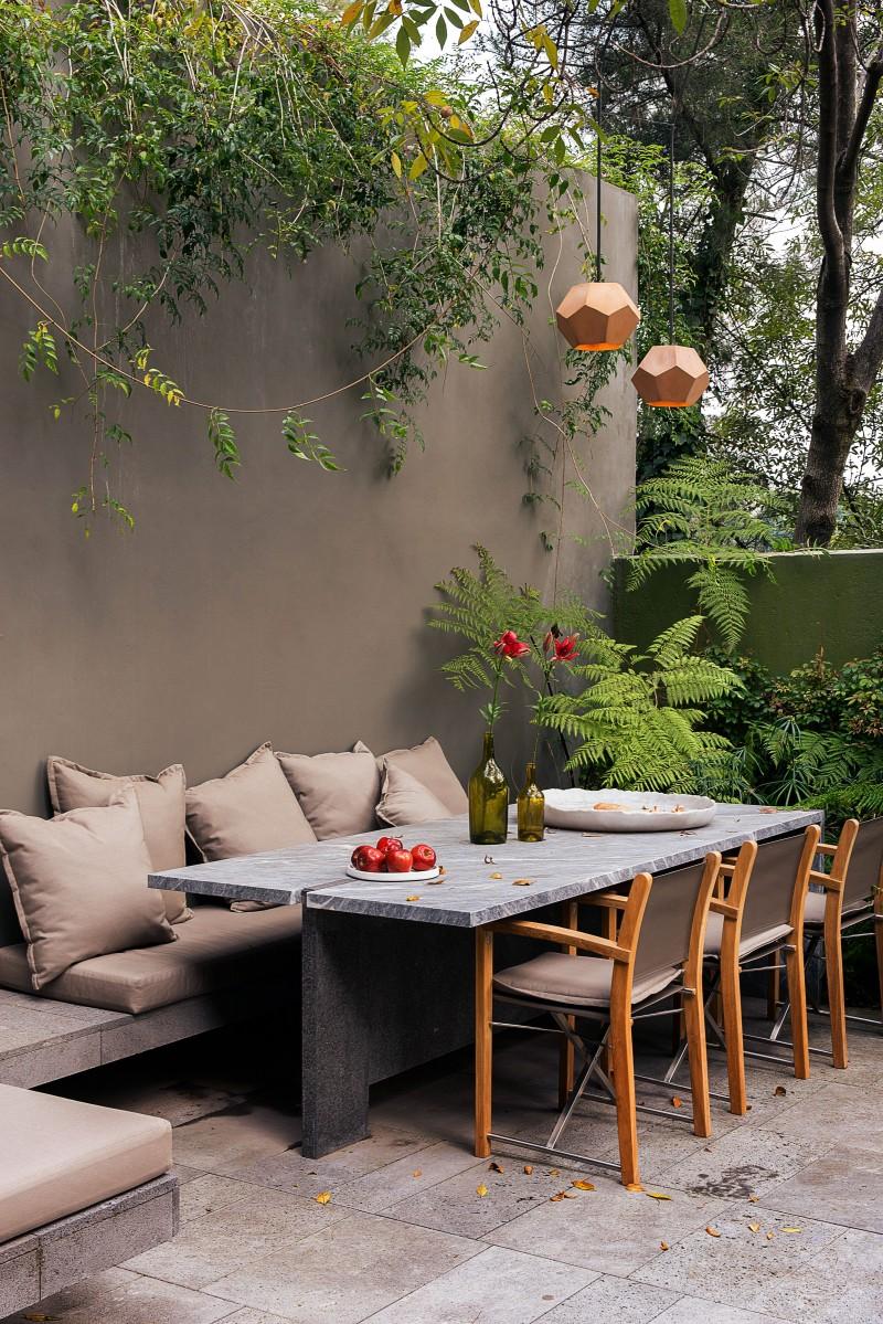 modern backyard with modern furniture set greenery concrete walls and concrete tile floors