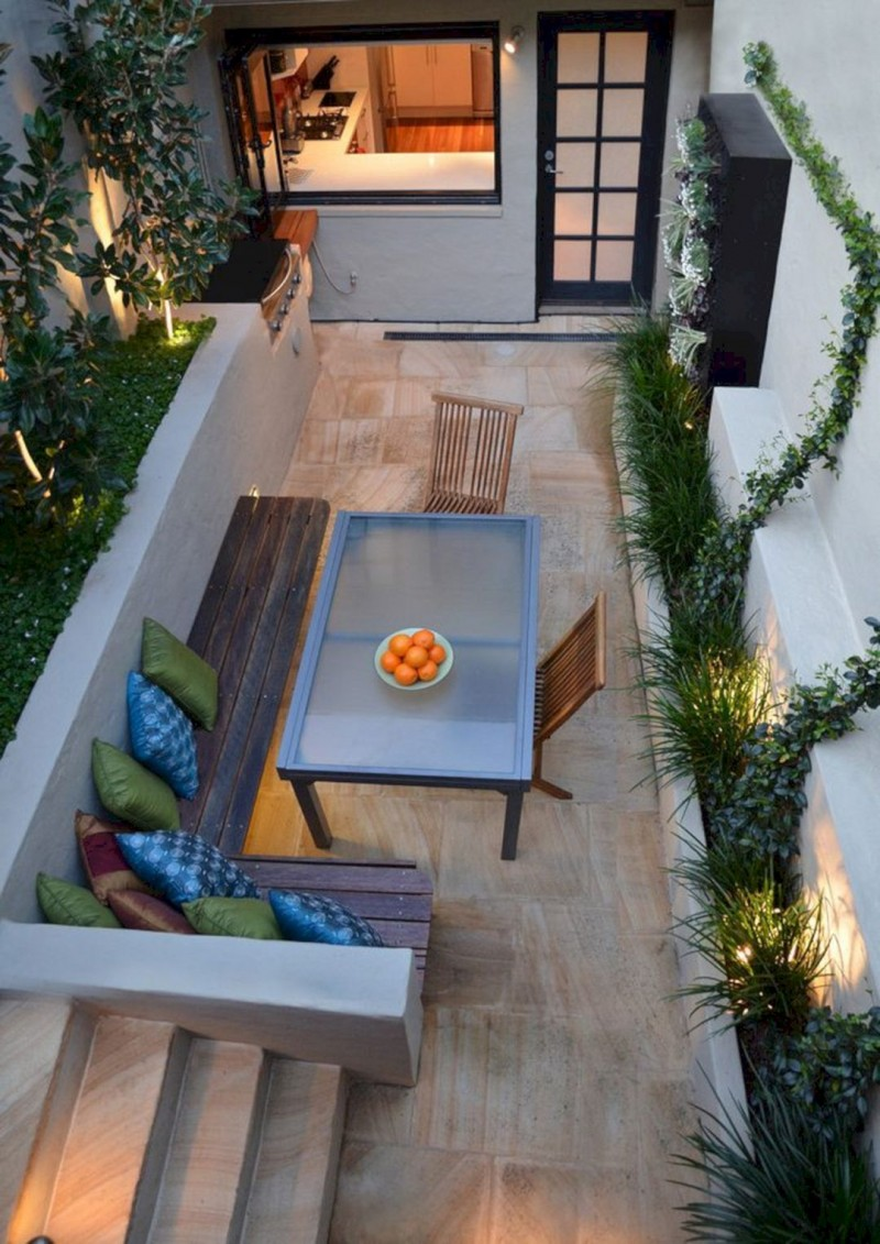 modern patio design with wood bench seat with colorful accent pillows blurred glass top table light wood floors ornate greenery with hidden lamps