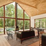 Open Concept Living Room And Eat In Kitchen With Gabled Roofs And Walls Glass Windows Midcentury Modern Furniture Set