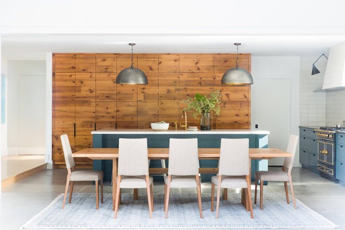 rustic midcentury modern dining space with wood wall panel white dining chairs kitchen island with blus shade white area rug modern rustic pendant lamps