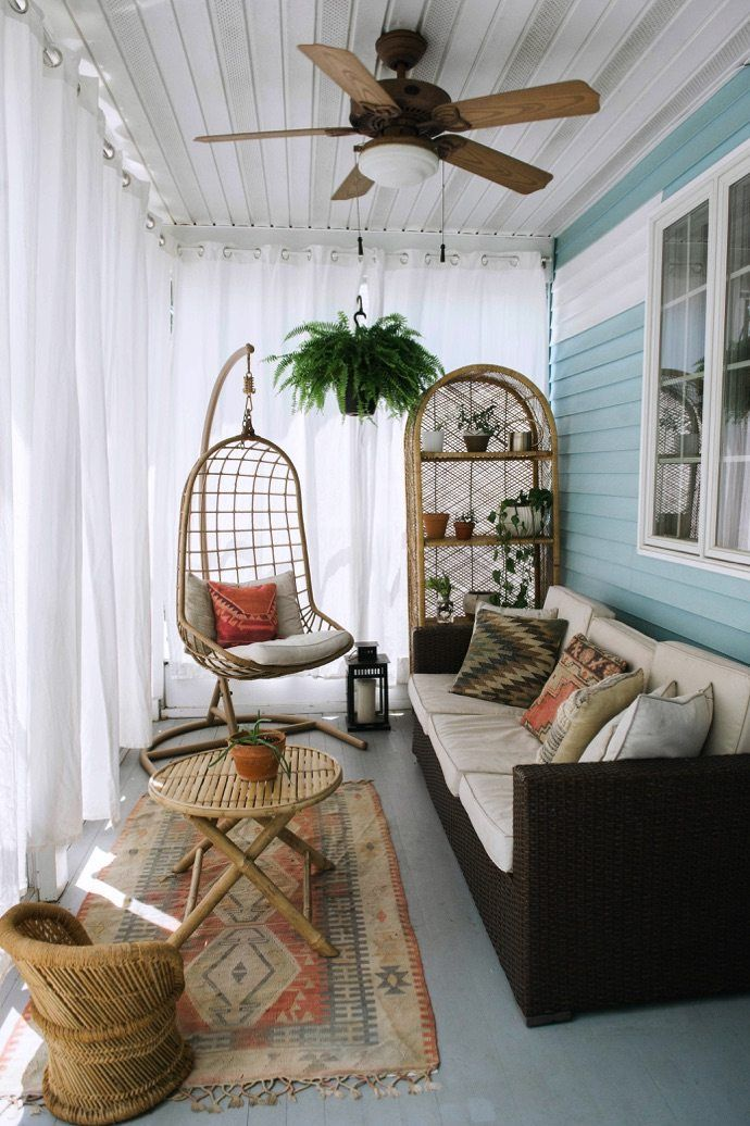 screened porch design with dark sofa with white cushions multicolored accent pillows worn out runner bamboo table with round top and x base rattan hanging chair with cushion and accent pillow
