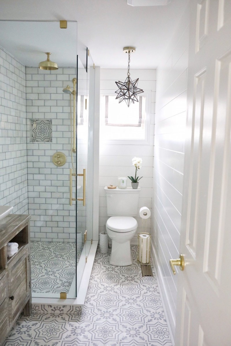 small and minimalist bathroom design with walk in shower with clear glass door vintage tile floors white subway tile walls white toilet