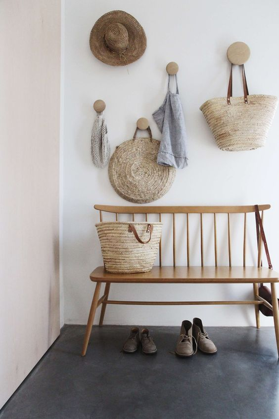 small entryway with simple wood bench with back flat woven wall ornaments dark concrete floors