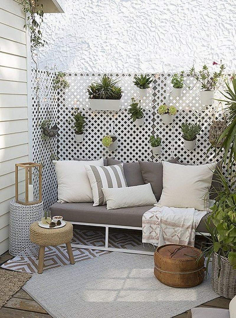 small patio dominated by white modern gray outdoor sofa gray runner white walls with potted greenery