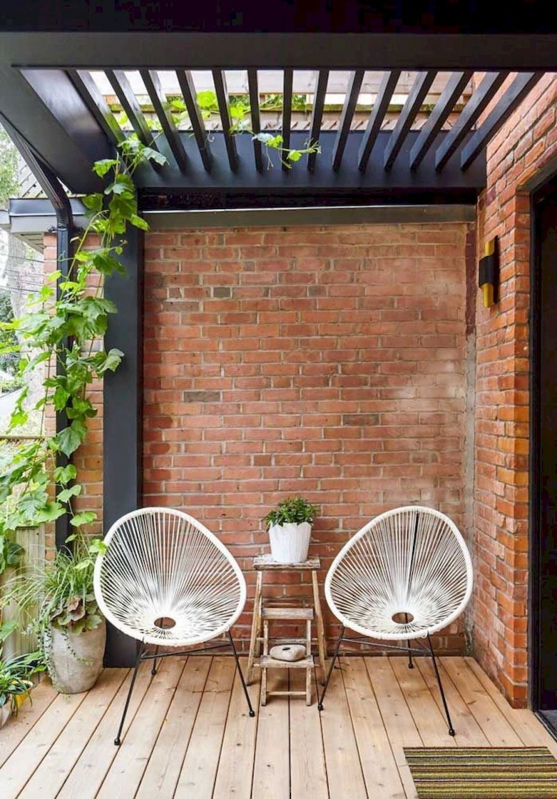 small patio with a couple of egg chairs in white rustic side tables red brick walls and wood plank floors