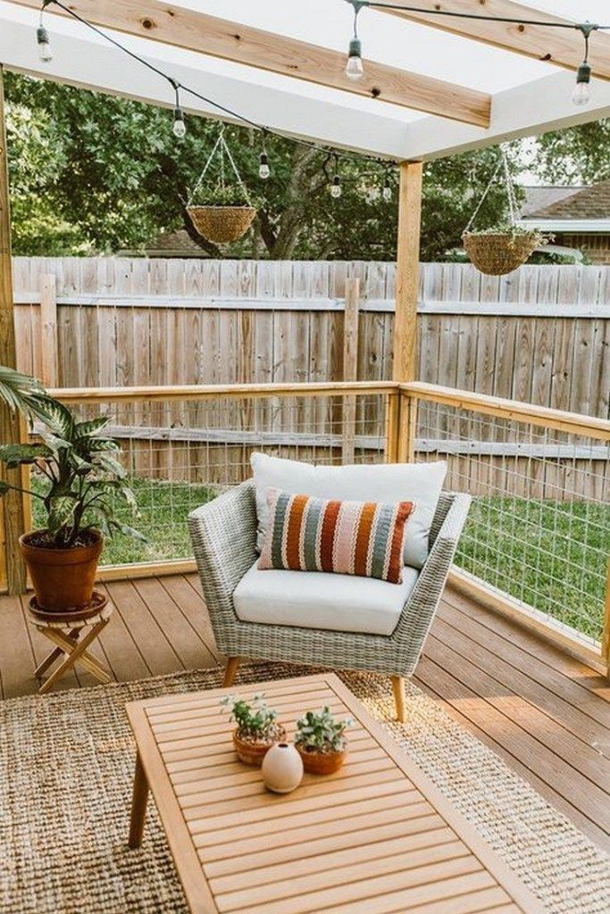 small patio with railings midcentury modern chair with accent pillow modern wood coffee table round top side table with x base wood plank floors