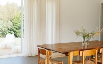 soft airy and minimalist dining space with natural wood dining furniture set soft toned area rug with tassels floor to ceiling draperies in white