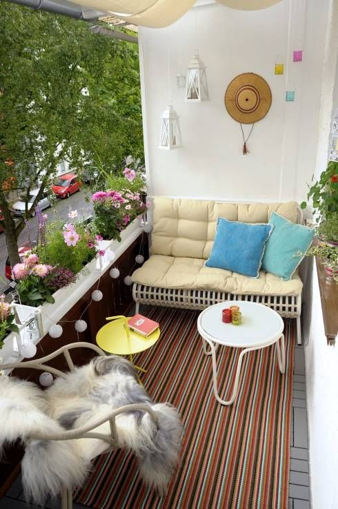 tiny balcony idea with white metal bench seat with back ultra soft yellow cushion blue throw pillows white and yellow round top tables rattan chair with shag cushion colorful stripes rug
