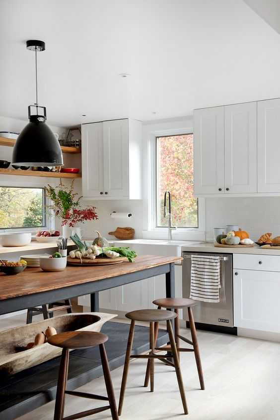 white kitchen cabinets wood top preparing table round top stools in midcentury modern style modern industrial pendant lamp