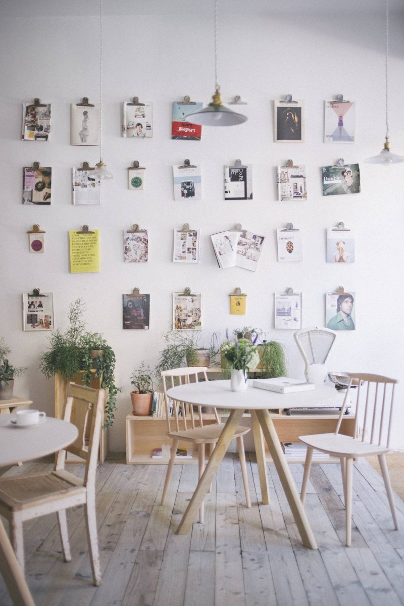 Scandinavian style coffee shop interior with light wood furniture sets lots of frames on walls light wood floors