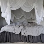 Beautiful Boho Bedroom With Layers Of White Bed Curtains And Layers Of Bedding Set