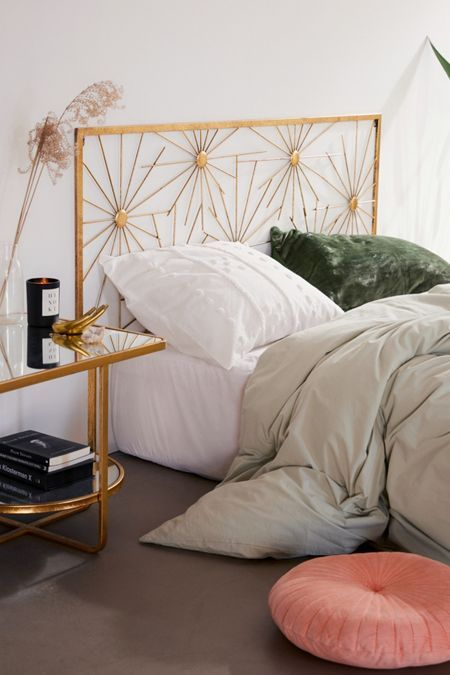chic Boho bedroom idea with metal bed frame with craft headboard brass framed bedside table with glass top white bedding set dusty white duvet cover coral floor cushion