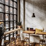 Coffee Shop Interior With White Brick Walls Industrial Style Window Floating Wooden Bench Table Natural Wood Stools Small Wood Tables White Bench Seat Wooden Floors