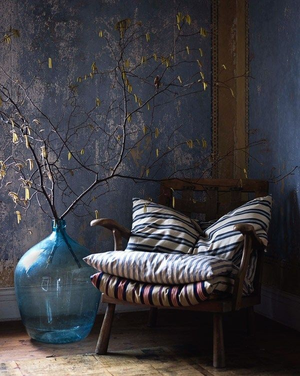 corner chair with dark wood frame and removable stripe cushions oversized glass pot for dry greenery