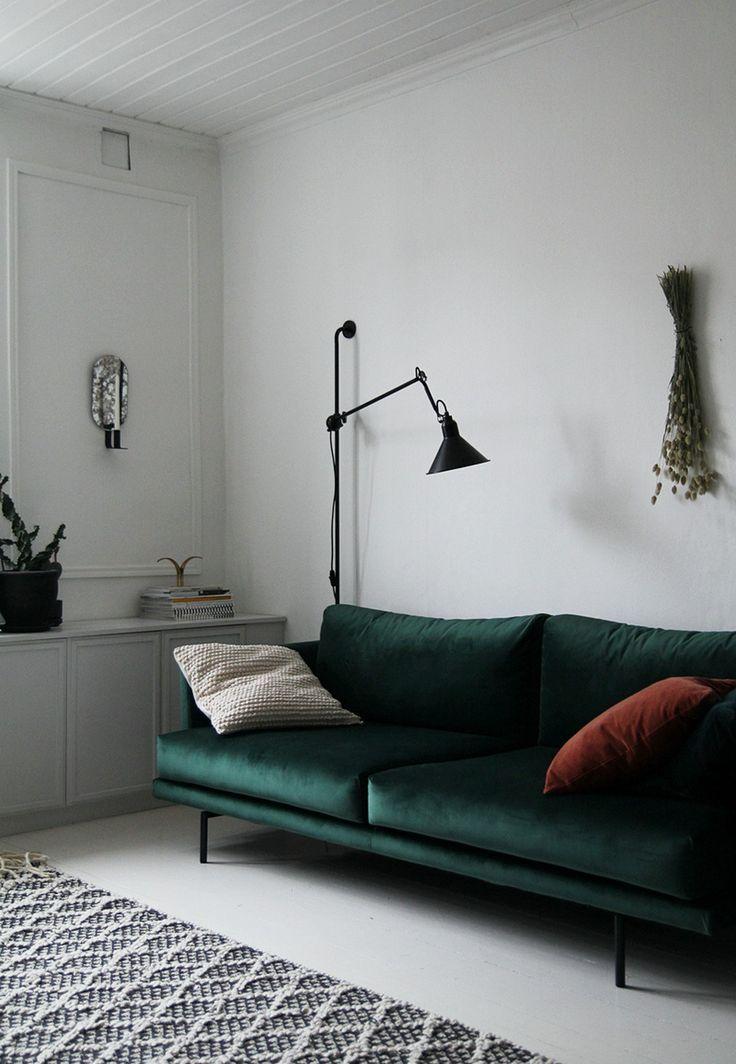 dark green velvet sofa with throw pillows textured area rug in gray