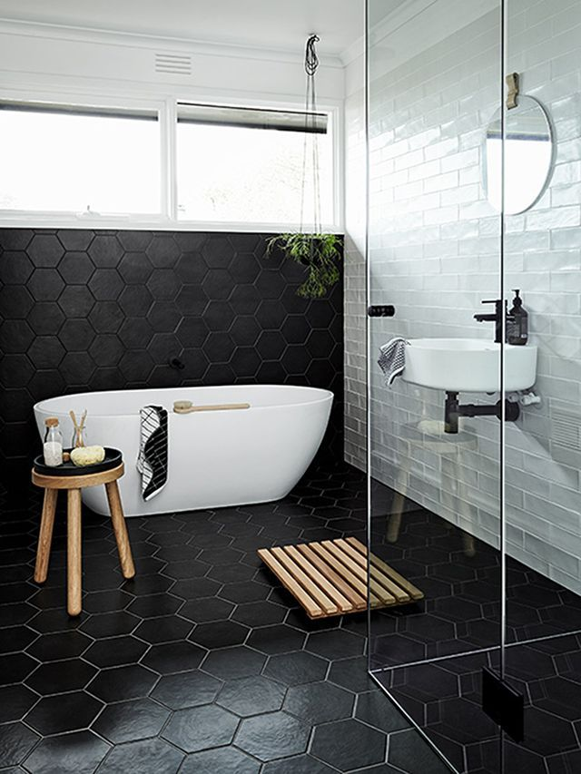 elegant black white bathroom with modern white bathtub wood stool with black round top clear glass shower door black hexagon tile walls and floors