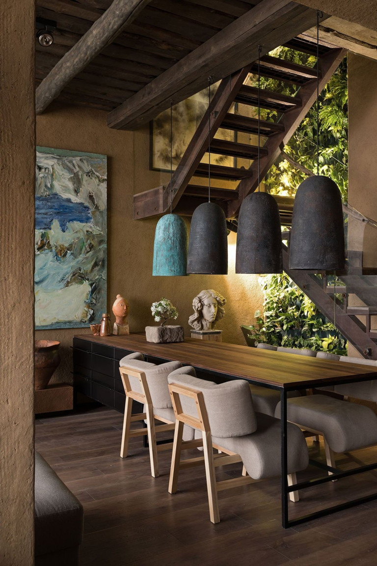 fancy Wabi sabi dining space with dark wood dining table wood framed dining chairs with gray cushions oversized pendants