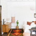 In White Bedroom With Bohemian Area Rug Moroccan Pouffe White Bedding Set Bohemian Pillows Light Wood Dresser Potted Greenery