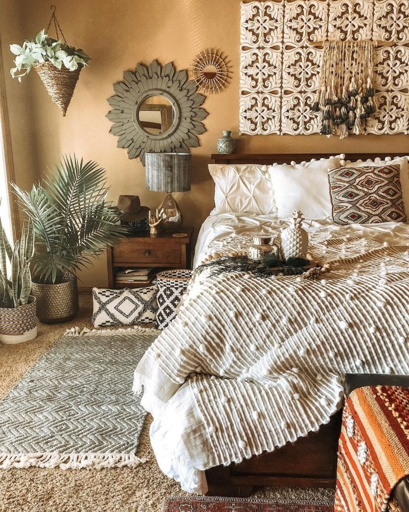 luxurious Boho style bedroom idea with layers of bedding set textural runner multicolored pillows wall mirror with hand craft frame houseplants on pots