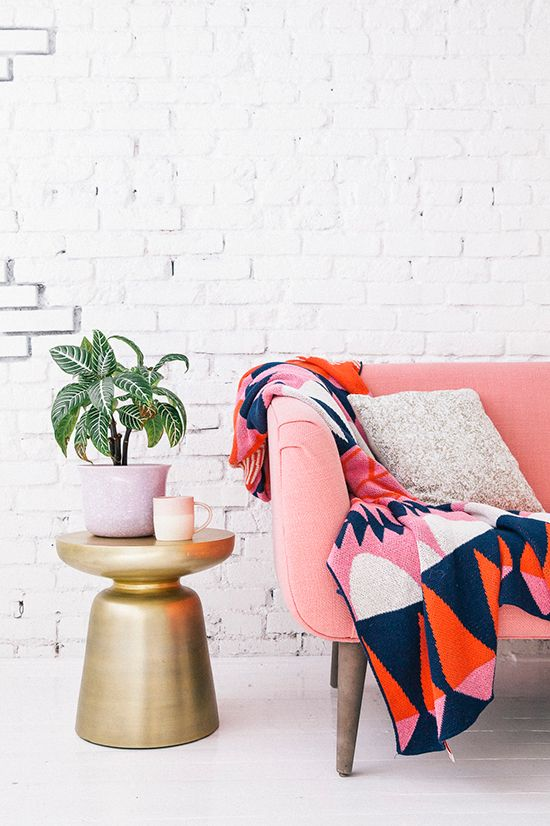 mid century modern couch in coral  gold side table colorful throw blanket