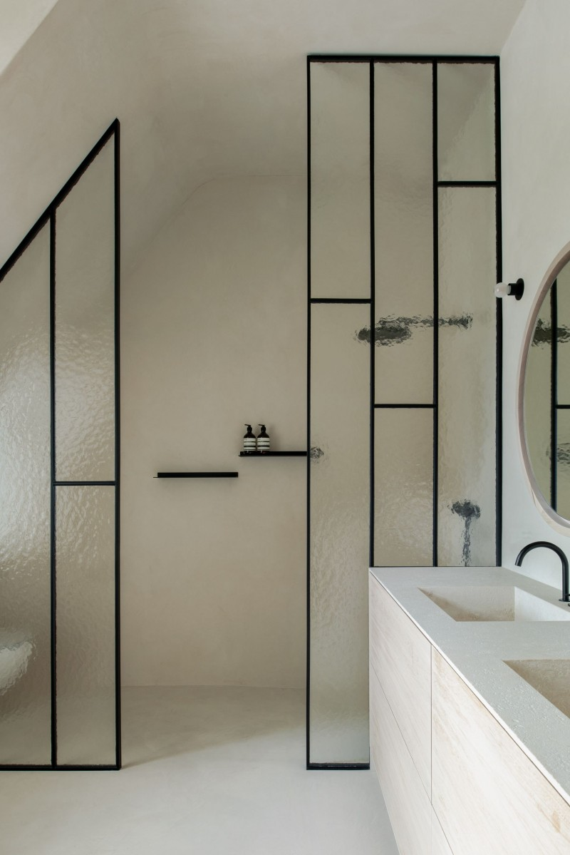 minimalist bathroom with blurry glass shower partition with black frames white bathroom vanity