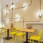 Minimalist Industrial Coffee Shop Interior With White Subway Tile Walls With Stunning Modern Industrial Lighting Installations Wood Top Tables Yellow Chairs