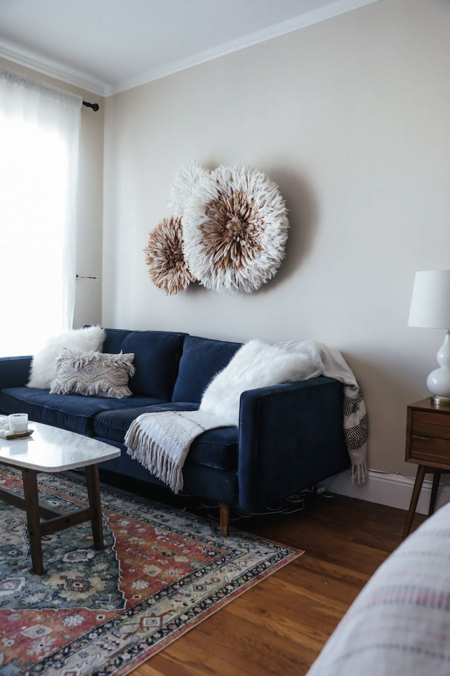 modern minimalist living room with navy blue sofa with throw blankets and throw pillows multicolored area rug white top coffee table hardwood floors Bohemian style wall decorations in round shape