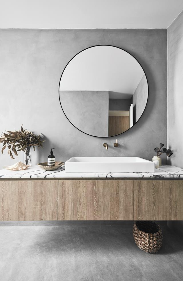 modern rustic bathroom design with natural wood countertop and marble top oversized wall mirror in round shape white sink