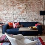 Navy Blue Sofa With Colorful Throw Pillows Boho Style Rug With Tassels Gray Chair Shabby Red Brick Walls