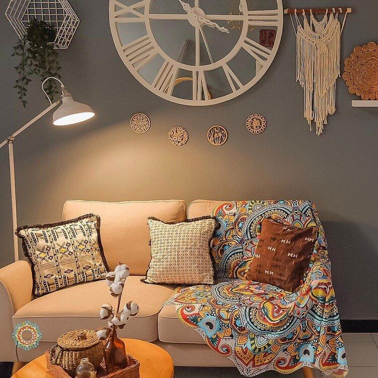 small sitting area in Boho style with soft sofa with multicolored throw blanket and throw pillows Boho style wall arts white floor lamp wooden coffee table